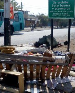 Basura es dejada debajo de cartel municipal, que advierte multas para quienes sean sorprendidos ensuciando la comuna